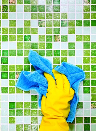 cleaning equipment: Hand in yellow protective glove  cleaning mosaic wall