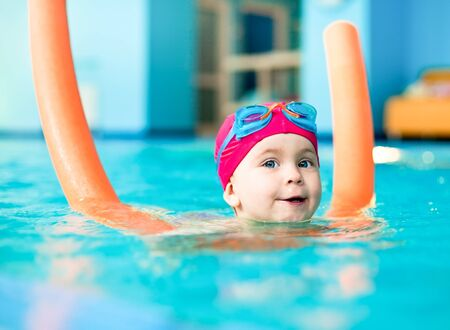 Happy little girl learning to swim with pool noodle photo