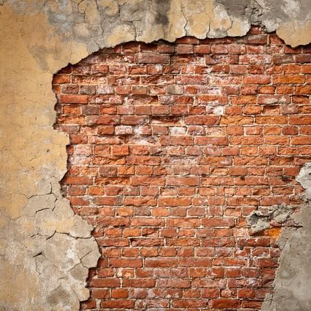 estuco: Antiguo fragmento de pared de ladrillo degradado