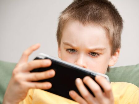 handheld: Young boy playing handheld game console