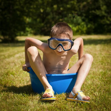 Boy wearing swimming mask sitting in a washbowl on a hot summer day Stock Photo - 7318673