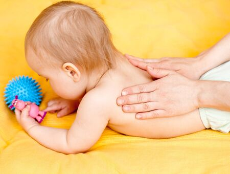 Masseuse massaging little baby girl, shallow focus photo