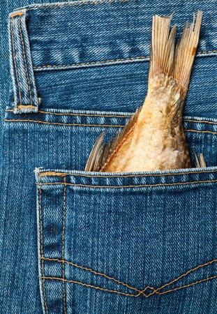 Blue jeans pocket with dried fish tail photo