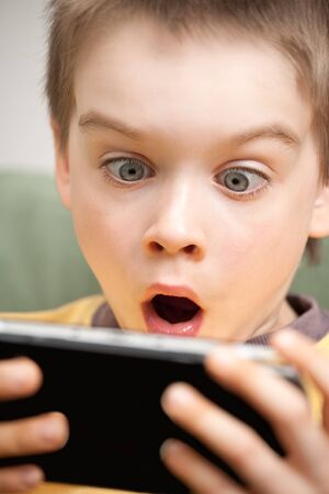Young boy playing handheld game console photo