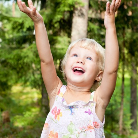 natural looking: Portrait of cute little girl with hands up in happiness