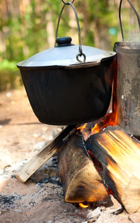 Camping kettles over burning campfire photo