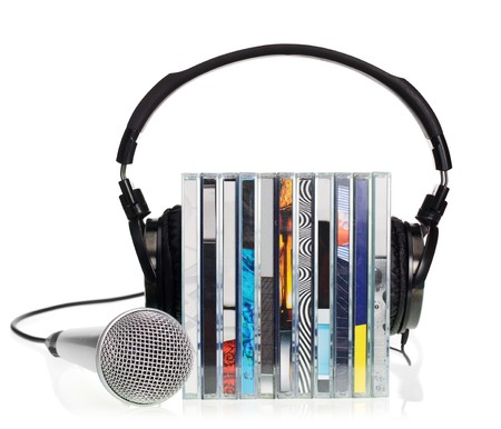 hifi: HI-Fi headphones on stack of CDs with microphone on white background