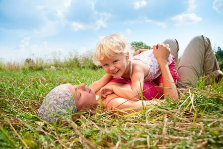 Young woman with cute little girl enjoying a summer day outdoors photo