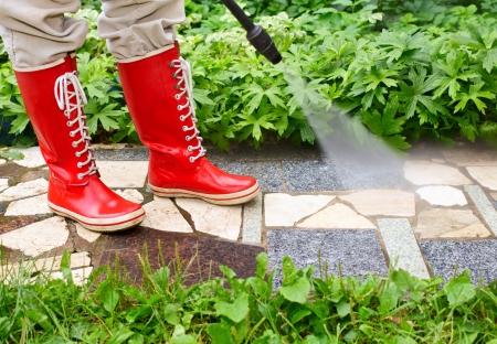 Persona en rojos gumboots callejón jardín con una arandela de presión de limpieza  Foto de archivo
