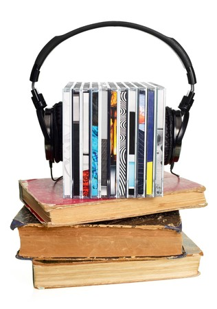 Stack of CDs with HI-Fi headphones and old books on white background photo