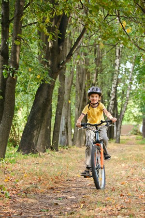 bicycle lane: Young boy riding bicycle in a park Stock Photo