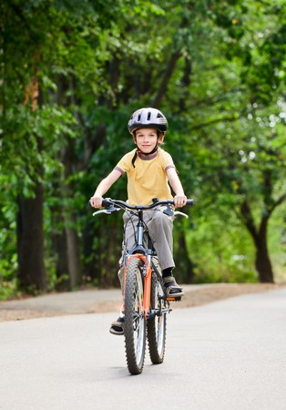 Young boy riding bicycle on a summer day photo