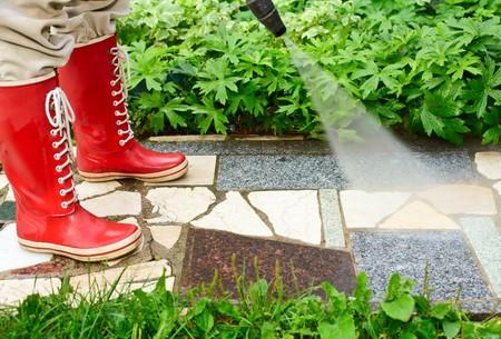 machine � laver: Personne en rouge gumboot nettoyage all�e de jardinage avec une rondelle de pression  Banque d'images