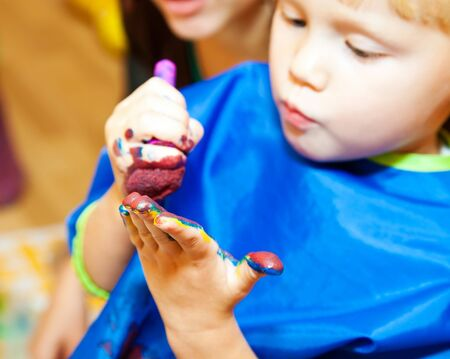 Little girl with paint brush making a finger painting Stock Photo - 7961811