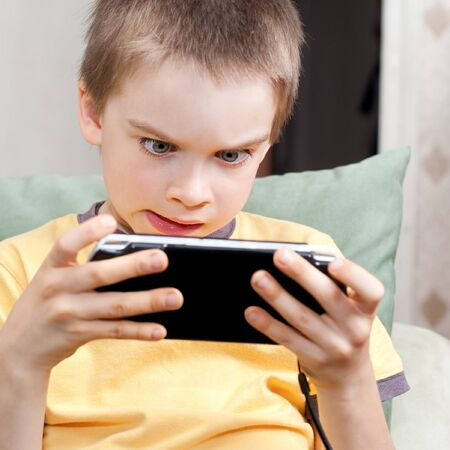 computer games: Young boy playing handheld game console