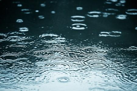 Gotas de lluvia recorridas en un charco con la reflexión de cielo azul  Foto de archivo