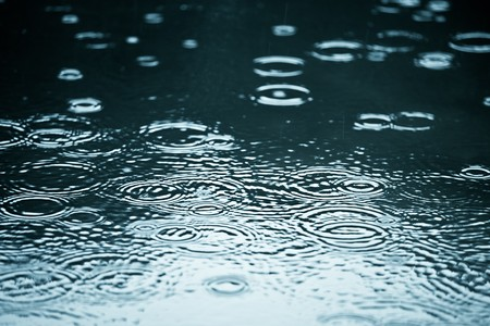 Rain drops rippling in a puddle with blue sky reflection photo