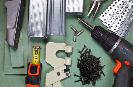 Plasterboard tools set with metal studs, screws, tape measure, rasp, screwgun and punch lock crimper photo
