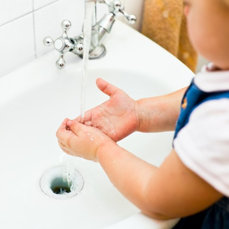 Little girl washing her hands in bathroom, shallow focus Stock Photo