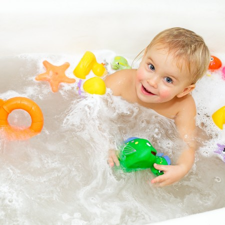 kids playing water: Cute little girl bathing with toys Stock Photo