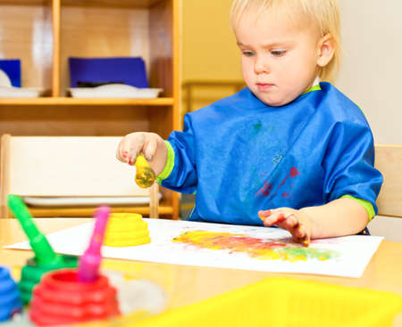 Little girl wearing blue apron painting with watercolors photo