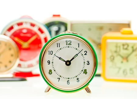 Vintage mechanical wind-up alarm clocks on white background, shallow focus photo