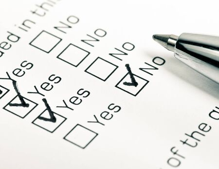 customer survey: Close up shot of filled check boxes with pen