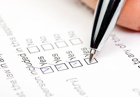 blank check: Hand with pen over blank check box Yes in application form Stock Photo