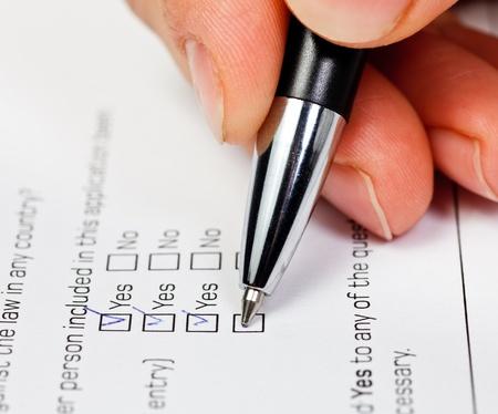Hand met pen over leeg selectie vakje Ja in inschrijvings formulier