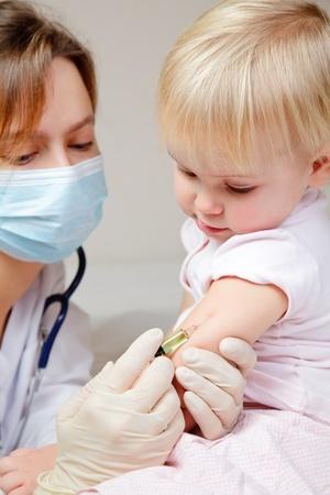 inyeccion intramuscular: Doctor dando una inyecci�n intramuscular de un ni�o en brazos Foto de archivo