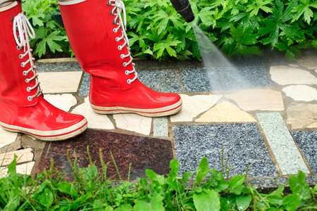 gumboots: Person in red  gumboots cleaning  garden alley with a pressure washer