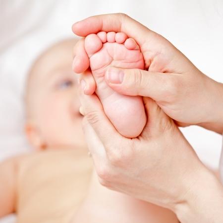 massaggio: Massaggiatore massaggiare i piedi del bambino piccolo, shallow focus