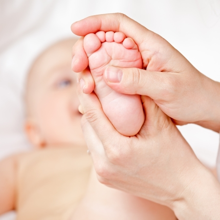 Masseur massaging little babys foot, shallow focus photo