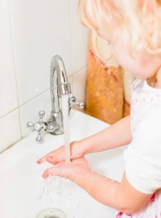 Little girl washing her hands in bathroom, shallow focus Stock Photo - 9215725