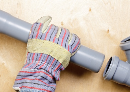 fitting: Plumbers hand wearing protective glove with pvc sewage pipes Stock Photo