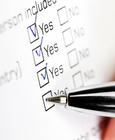 checkbox: Mano con penna su casella di assegno in bianco, s�, nel modulo di domanda
