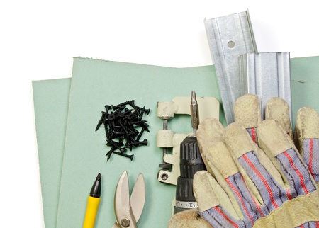 Plasterboard tools set with metal studs, screws, screwgun, punch lock crimper, tin snip cutter and protective gloves on white background photo
