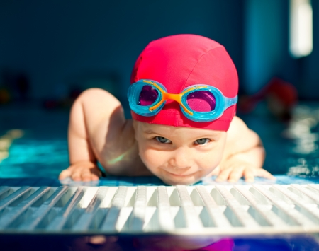 Happy little girl looking out from swimming pool, focus on googles