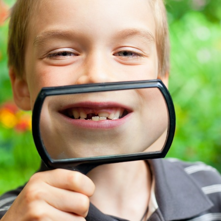Young boy showing missing baby tooth through hand magnifier photo