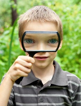 thru: Young boy looking thru hand magnifier Stock Photo