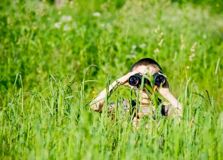 schoolkid search: Young boy in a field looking through binoculars Stock Photo