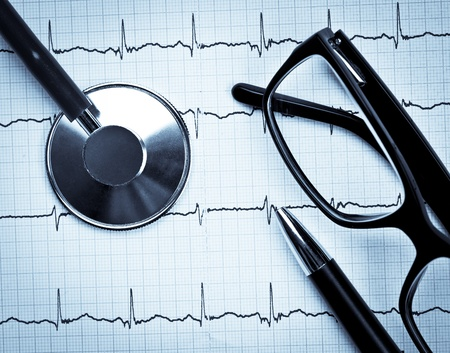 diagnostics: Stethoscope and glasses lying on ECG diagram