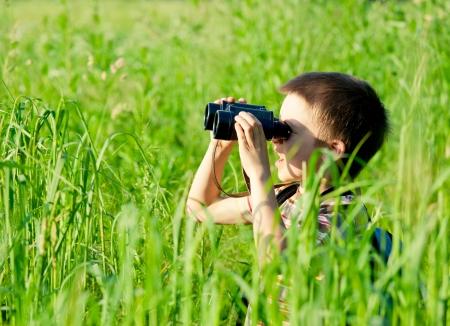 schoolkid search: Joven en un campo a trav�s de binoculares Foto de archivo