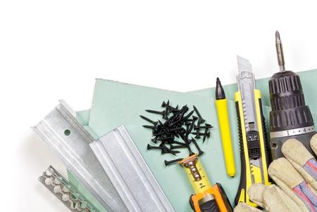 Plaques de plâtre, des outils, des poteaux métalliques, vis et des gants de protection sur fond blanc