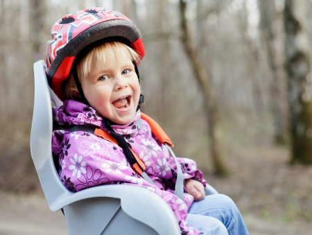 helmet seat: Happy little girl wearing helmet sitting in bycicle child seat