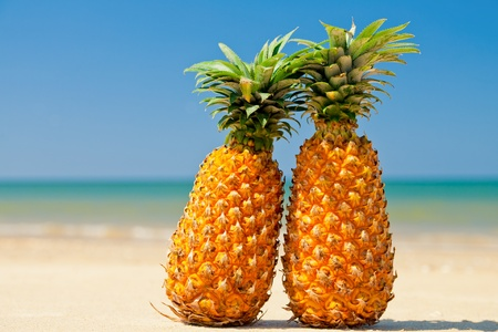 Two ripe pineapples on the sandy shore against clear blue sky