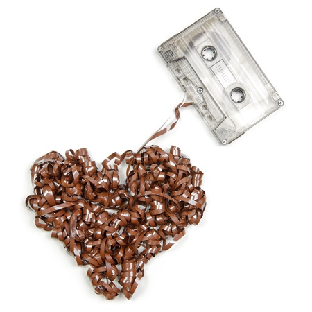 unwound: Vintage transparent Compact Cassette with pulled out tape in the shape of heart on white background Stock Photo
