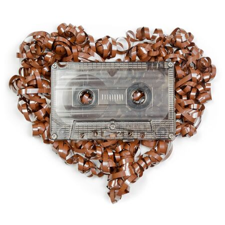 Vintage transparent Compact Cassette with pulled out tape in the shape of heart on white background photo