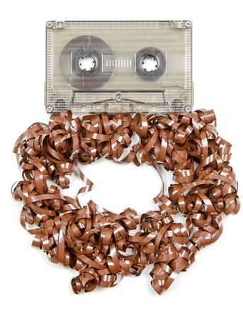 unwound: Vintage transparent Compact Cassette with pulled out tape on white background