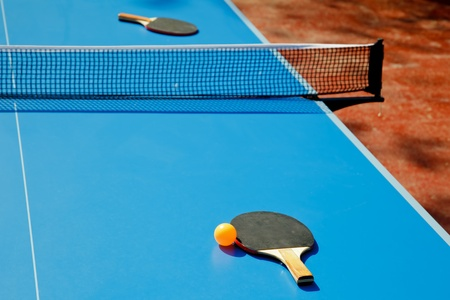 Ping pong ball with paddle on tennis table photo
